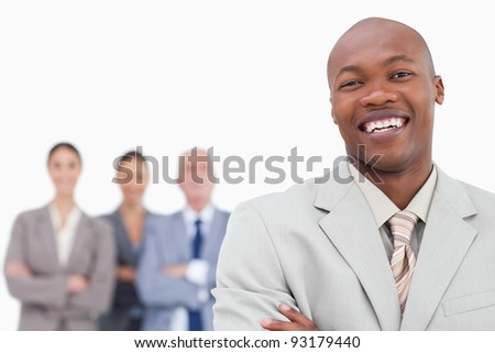 Smiling salesman with team behind him against a white background - stock photo