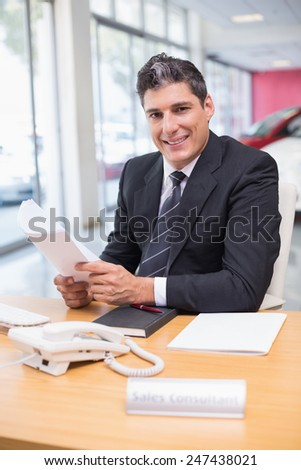 Smiling salesperson holding a document at new car showroom - stock photo