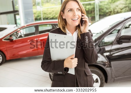 Smiling saleswoman having a phone call at new car showroom - stock photo