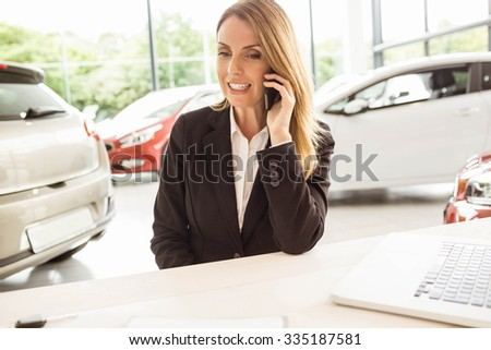 Smiling saleswoman having a phone call at new car showroom