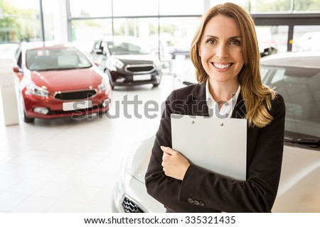 Smiling saleswoman holding document while looking at camera at new car showroom - stock photo