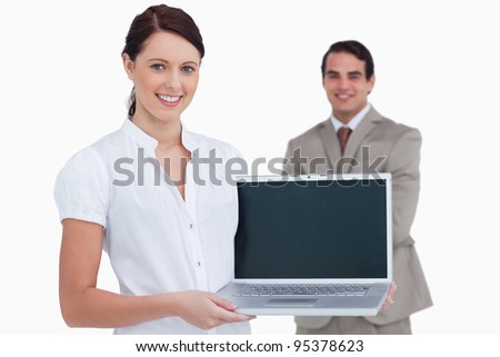 Smiling saleswoman presenting laptop screen with colleague behind her against a white background - stock photo