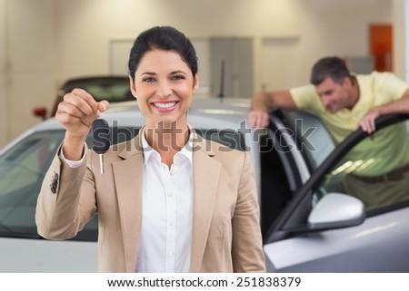 Smiling saleswoman showing a customer car key at new car showroom - stock photo