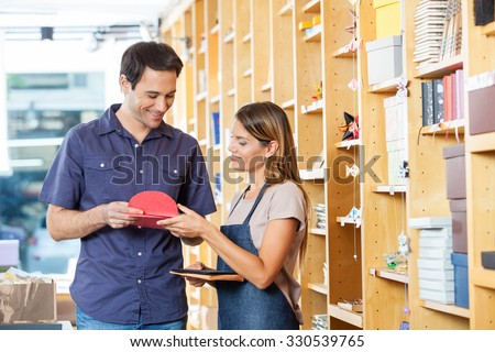 Smiling saleswoman showing greeting cards to male customer in shop - stock photo