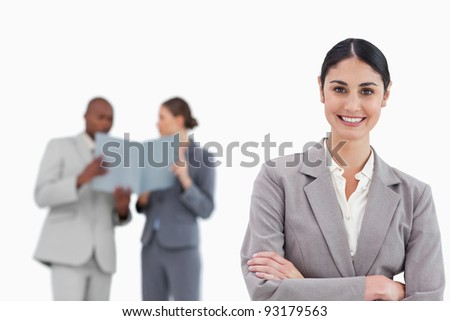 Smiling saleswoman with arms crossed and colleagues behind her against a white background