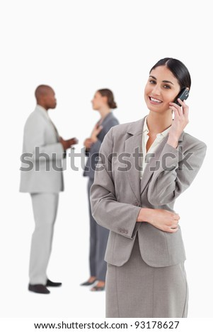 Smiling saleswoman with cellphone and colleagues behind her against a white background
