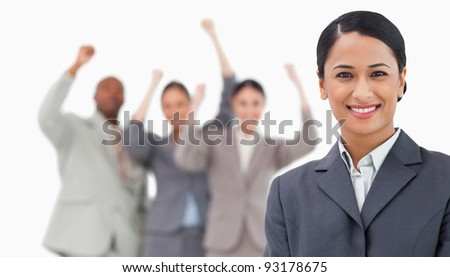 Smiling saleswoman with cheering colleagues behind her against a white background - stock photo