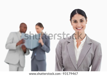 Smiling saleswoman with co-workers behind her against a white background
