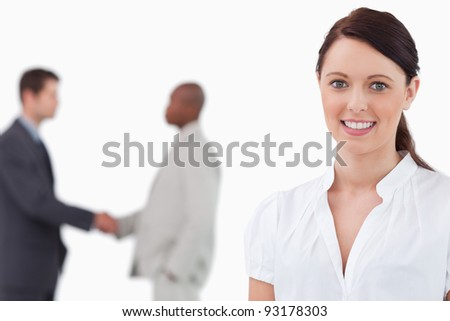 Smiling saleswoman with hands shaking trading partners behind her against a white background