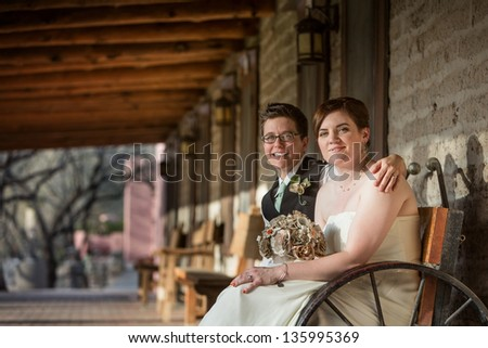 Smiling same sex married partners sitting together - stock photo