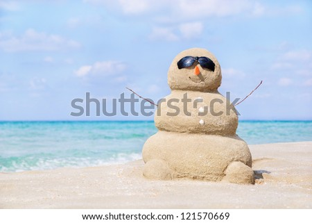 Smiling sandy happy man in sunglasses on the sea beach against blue cloudy summer sky - travel concept - stock photo
