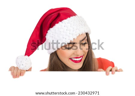 Smiling Santa Girl peeking behind a white banner and looking down. Studio portrait isolated on white. - stock photo