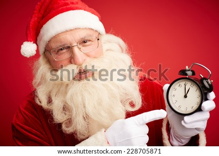Smiling Santa holding clock showing five minutes to twelve - stock photo
