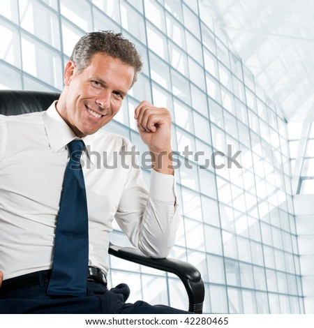 Smiling satisfied businessman looking at camera sit in his chair at office - stock photo