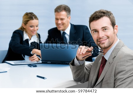 Smiling satisfied businessman looking at camera with his colleagues in the background during a meeting in the office - stock photo