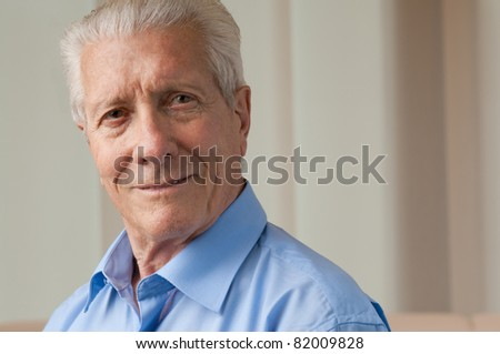 Smiling satisfied senior man looking at camera at home, copy space - stock photo
