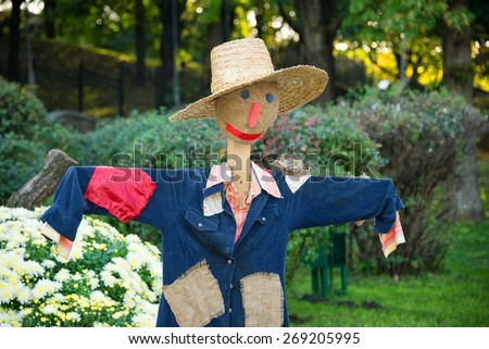 Smiling scarecrow in a vegetable garden in a countryside
