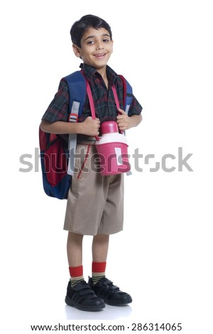 Smiling school boy standing with book bag and water bottle against white background - stock photo