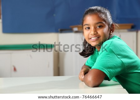 Smiling school girl at class desk in green t-shirt