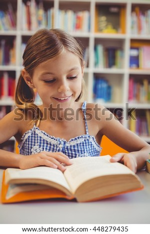 Smiling school girl reading a book in library at school - stock photo