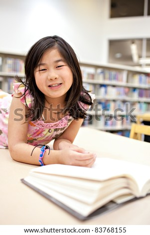 Smiling School Girl Reading Book at Library, Shallow DOF - stock photo