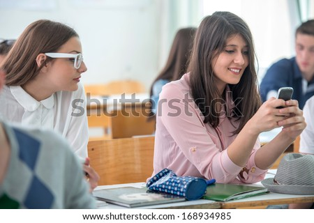 Smiling school girl typing on cellphone in classroom - stock photo
