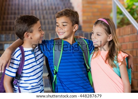Smiling school kids standing with arm around at school - stock photo