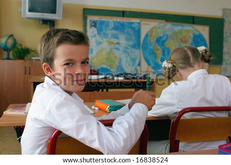 Smiling schoolboy at a lesson at school. - stock photo