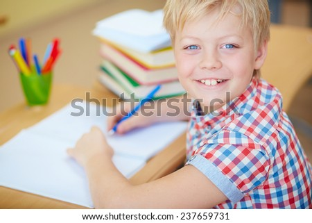 Smiling schoolboy looking at camera by his workplace - stock photo