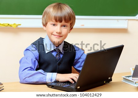 Smiling schoolboy studying with his laptop at classroom.