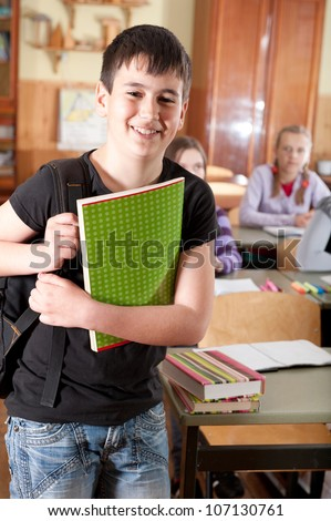 Smiling schoolboy with notebook in front of class - stock photo