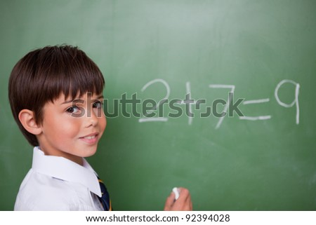 Smiling schoolboy writing an addition on a chalkboard - stock photo