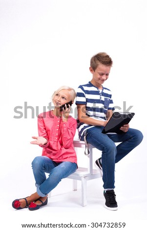smiling schoolchildren learn about the world and communicate with the help of modern tablets and phones, an interesting training and gadgets.Photo from the depth of field on a white background