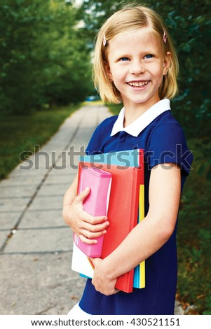 smiling schoolgirl in a blue school dress, with books. - stock photo