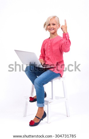 Smiling schoolgirl learns and communicates with the help of modern tablets and phones, an interesting training and communication gadgets. Photo from the depth of field on a white background. - stock photo