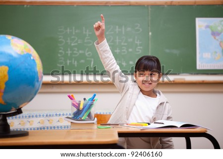 Smiling schoolgirl raising her hand to answer a question in a classroom - stock photo