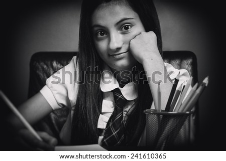Smiling schoolgirl sits at a school desk with hand in jaw, writes homework smiling at camera. Black & white picture. - stock photo