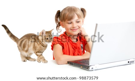smiling schoolgirl sitting at notebook with kitten - stock photo