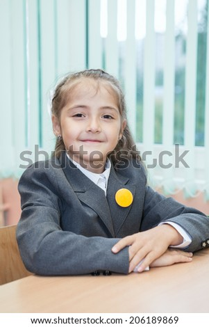 Smiling schoolgirl sitting at the school desk - stock photo
