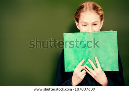Smiling schoolgirl standing near the blackboard with a book. Education. - stock photo