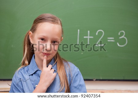 Smiling schoolgirl thinking in front of a blackboard - stock photo