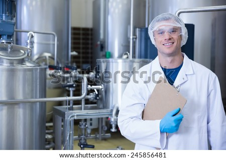 Smiling scientist looking at camera holding a clipboard in the factory - stock photo