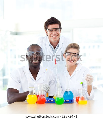 Smiling scientists examining test-tubes in a laboratory - stock photo