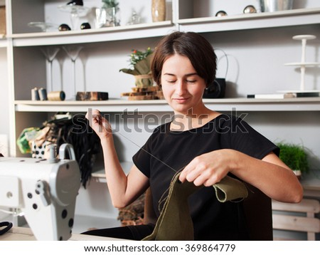 smiling seamstress sewing clothes. Workplace of tailor - sewing machine, rolls of thread, fabric. - stock photo