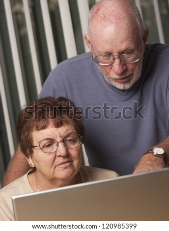 Smiling Senior Adult Couple Having Fun on the Computer Laptop Together. - stock photo
