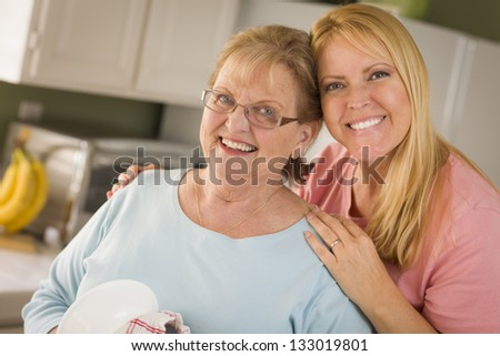 Smiling Senior Adult Woman and Young Daughter At Sink in Kitchen. - stock photo
