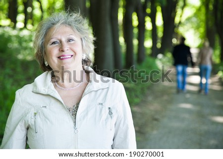 smiling senior aged woman outdoors with blurred walking couple  - stock photo