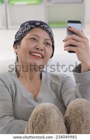 Smiling senior asian thai  woman using cell phone - stock photo