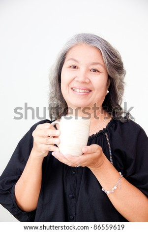 smiling senior asian woman holding a cup - stock photo