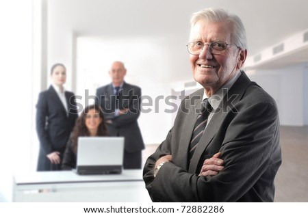 Smiling senior boss with business team on the background - stock photo